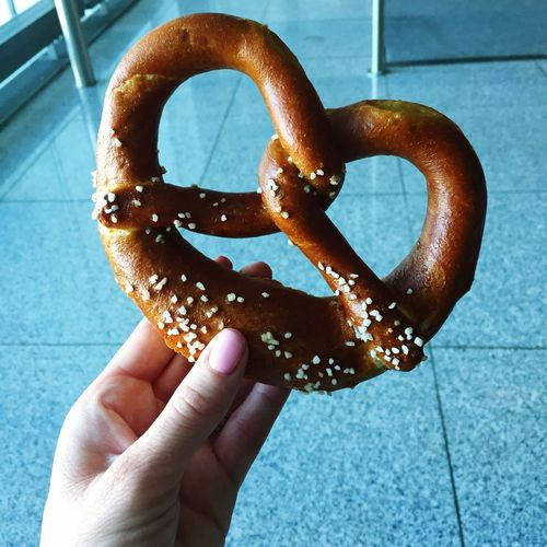Cropped image of hand holding pretzel