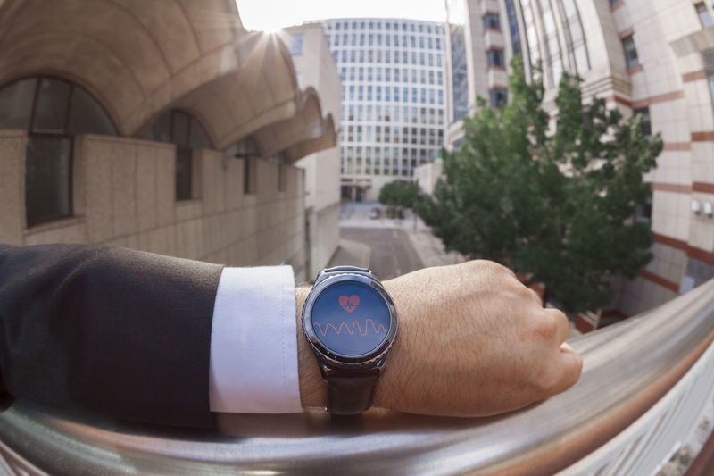 Close-up of businessman wearing wristwatch in city