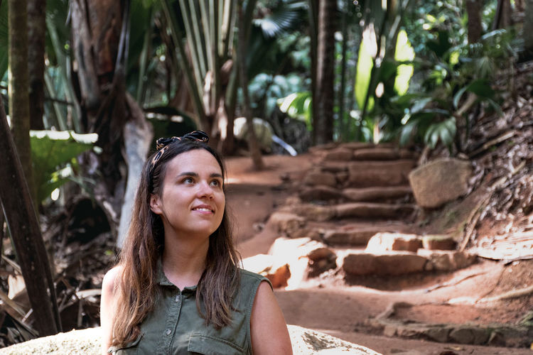 Portrait of an attractive young woman in tropical forest.