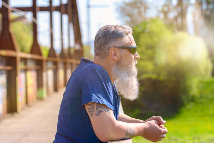 Side View Of Bearded Man Wearing Sunglasses At Park