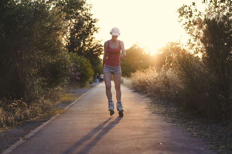 Young woman having fun while roller skating outdoors during female wearing a pale pink cap and sports clothes doing exercise with her headphones on listening to the music. Casual Clothing Day Diminishing Perspective Direction Footpath Full Length Leisure Activity Lens Flare Lifestyles Nature One Person Outdoors Plant Real People Rear View Road Shorts Sky Sunlight The Way Forward Transportation Tree Walking