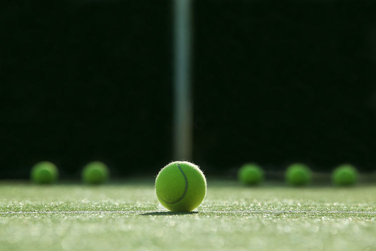 Close-up of tennis balls on field in court