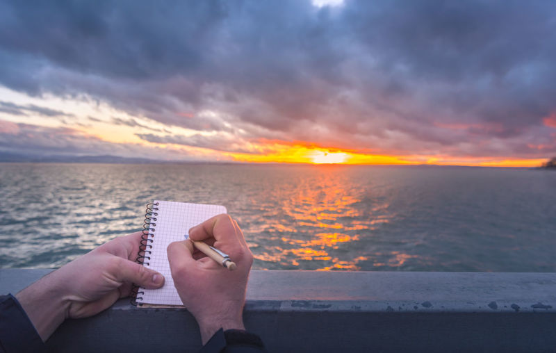 Close-Up Of Hand Writing In Note Pad Against Sea And Sky During Sunset