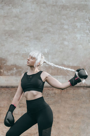 Portrait of woman with boxing gloves standing against wall