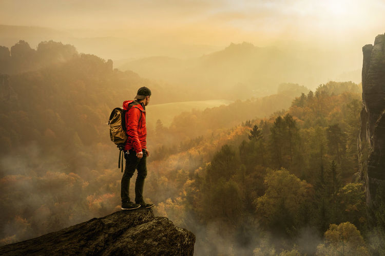 rear view of man standing on mountain against sky Hiking Lifestyle Nature Rear View Standing The Great Outdoors - 2018 EyeEm Awards Tranquility Beauty In Nature Fog Idyllic Leisure Activity Looking At View Men Mountain Non-urban Scene One Person Outdoors Real People Scenic Nature Sky