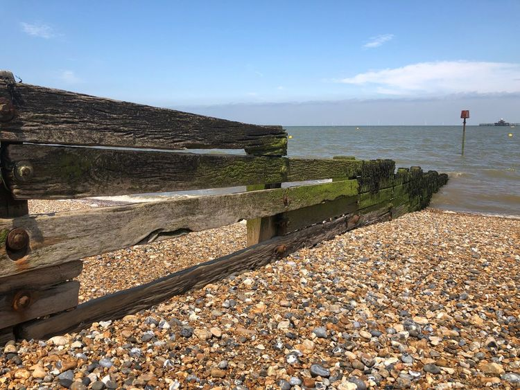 Weathered Coastline Coast Seaside Wooden Texture Wooden Pebble Beach England Beachphotography Divide Groyne Water Sea Sky Sunlight Beach Tranquility Nature Pebble