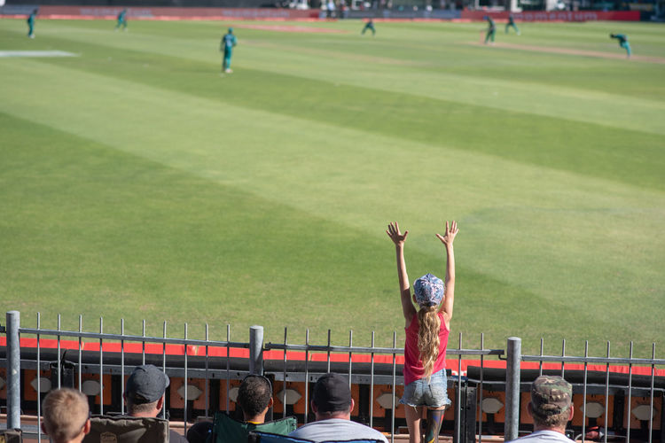 Rear view of girl with arms raised enjoying at stadium