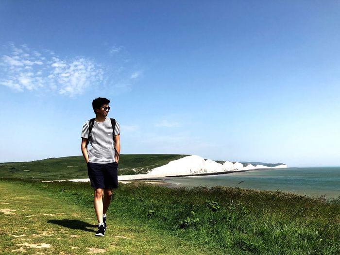 Full length of man walking on field against blue sky