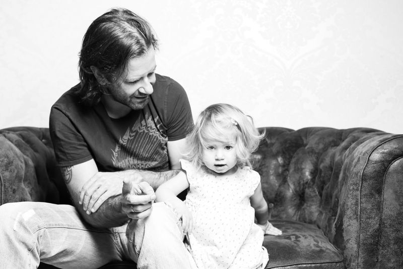 Father With Little Daughter Sitting On Sofa At Home