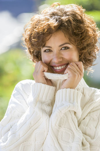 Close-Up Portrait Of Smiling Woman Wearing Sweater