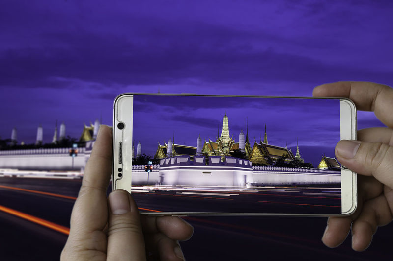 Photographing with smartphone in concept and temple of the Emerald Buddha.(Wat Phra Kaew.) Bangkok, Thailand with twilight time Emerald Buddha Temple Twilight Time Wat Phra Kaew Body Part Buddhism Close-up Cloud - Sky Communication Connection Finger Hand Holding Human Body Part Human Finger Human Hand Nature One Person Personal Perspective Purple Real People Sky Smartphone Technology Unrecognizable Person Wireless Technology