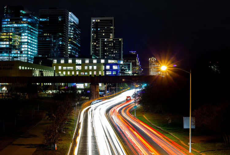 Car in Traffic Illuminated Night City Street Long Exposure Speed Building Exterior Architecture Motion Multiple Lane Highway Light Cityscape Office Building Exterior Glowing Traffic City Life Blurred Motion Nature Outdoors Street Light Road Light Trail Transportation Built Structure Highway
