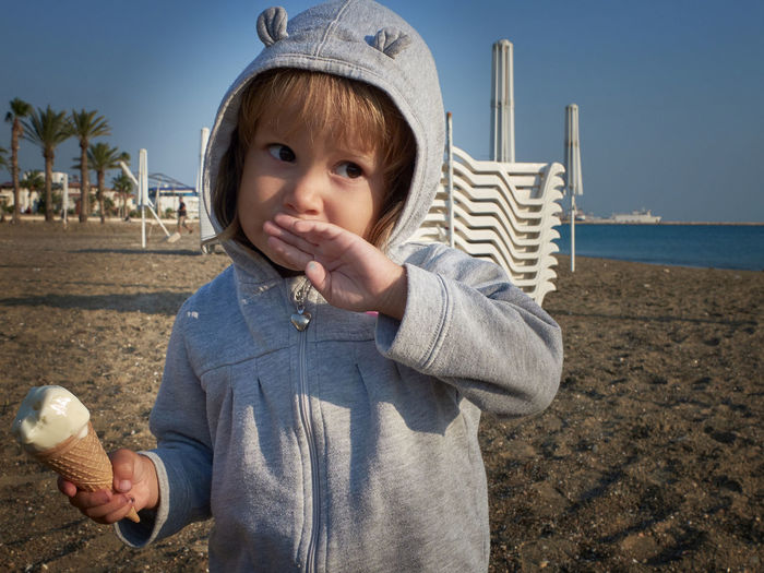Thoughtful little girl wipes her mouth with back of her hand while eating ice cream on a sea beach