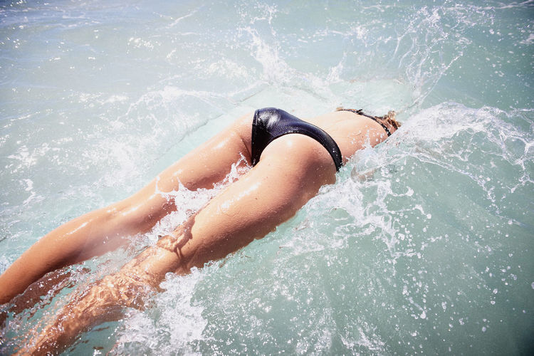 Midsection of woman in bikini diving in sea on sunny day