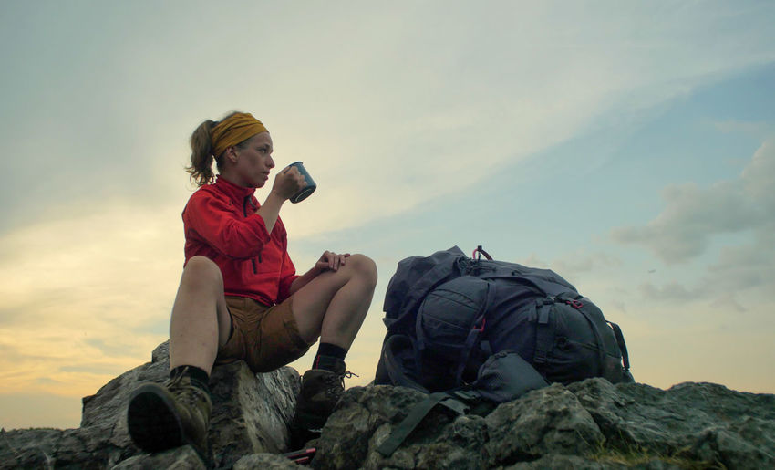 caucasian female hiker sitting on a rocky peak next to a backpack drinking beverage out of a mug Alpine Backpacking Boots Camping Expedition Freedom Hiking Nature Sitting Travel Trekking Woman Active Activity Adventure Backpack Beauty In Nature Casual Clothing Cloud - Sky Female Full Length Hobby Holding Leisure Activity Lifestyles Mountain Nature One Person Outdoors Peak People person Real People Rock Rock - Object Sitting Sky Solid Teenager Trek Young Adult