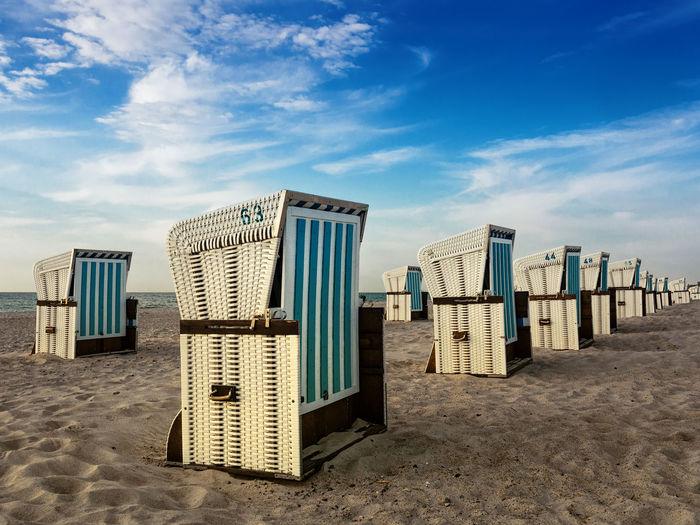 Hooded beach chairs on sand at beach against cloudy sky