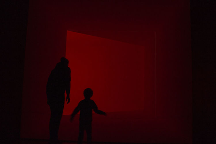 Silhouette boy standing against red wall