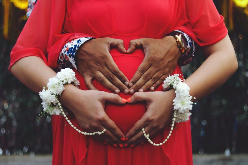 Pregnant woman and man making heart shape with hands on her stomach