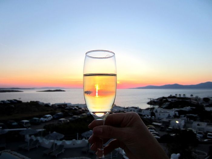 Cropped image of hand holding champagne flute at mykonos during sunset