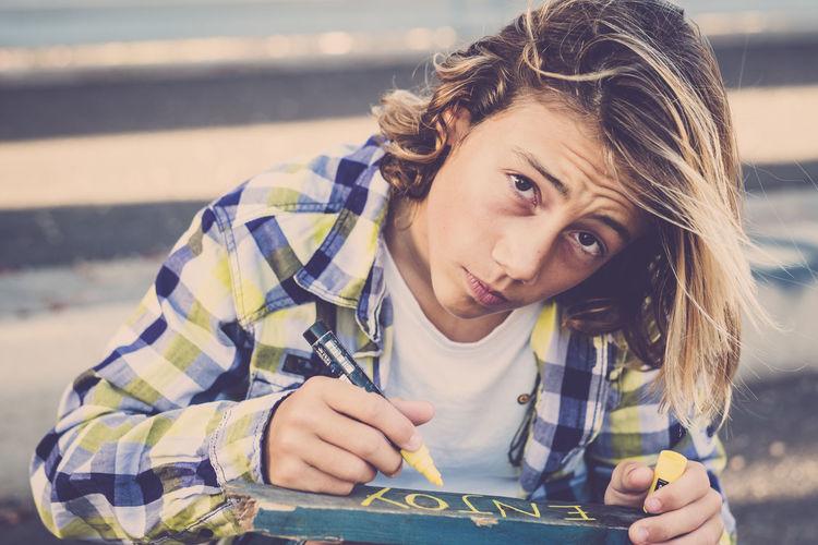 Portrait of boy writing on wood