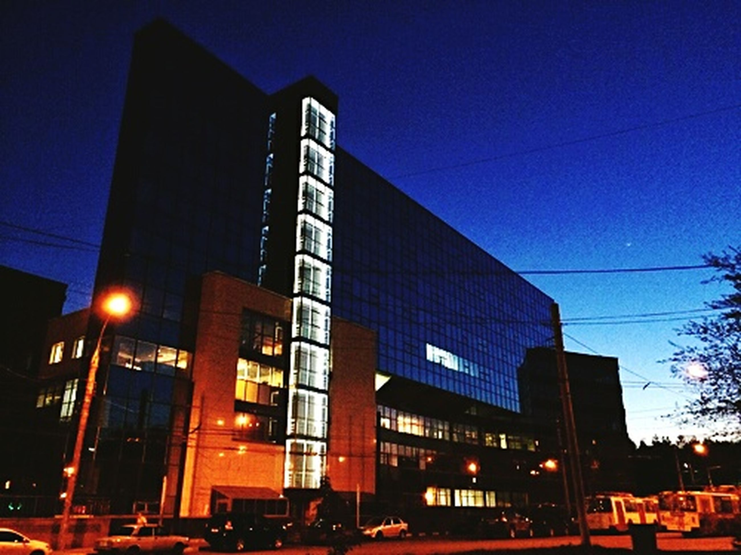 building exterior, architecture, built structure, illuminated, low angle view, city, building, night, street light, sky, residential building, modern, city life, office building, window, lighting equipment, residential structure, outdoors, dusk, no people