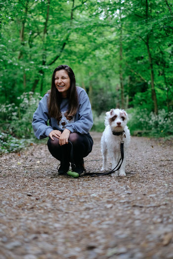 Portrait of woman with dog sitting in forest