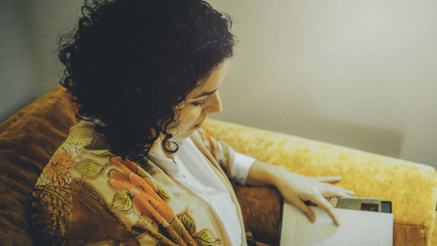 One Person Indoors  Real People Lifestyles Sitting Focus On Foreground Young Adult Leisure Activity Women Home Interior Hair Hairstyle Young Women Adult Casual Clothing Curly Hair Black Hair Looking Furniture Contemplation Beautiful Woman Reading Reading A Book Relaxing Relaxing Moments