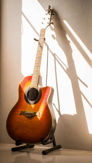 Close-up of guitar against wall at home