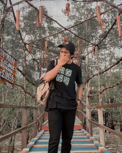 Young man standing on footbridge