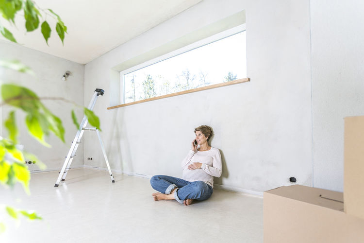 Young woman using phone while sitting on wall