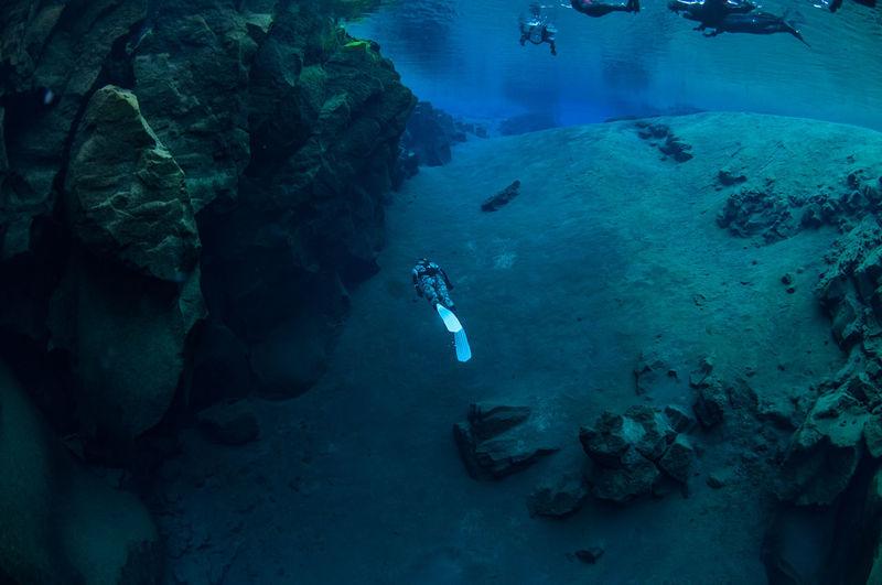Scuba Divers Swimming In Sea