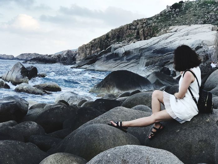 Rear view of woman sitting on cliff by sea