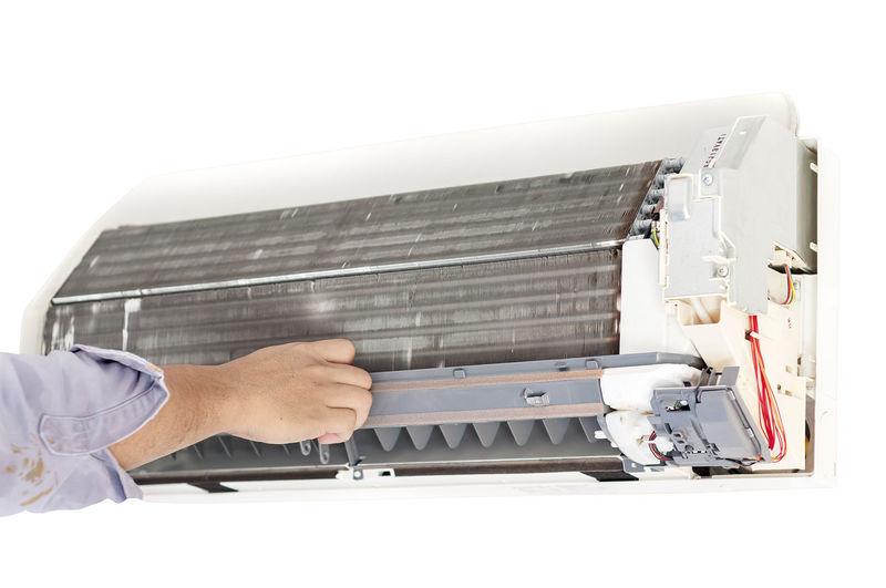 Cropped hand of man repairing air conditioner