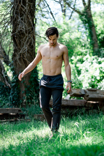 Full length of shirtless young man standing on grass
