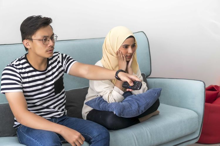 Young Malay Couple at the Sofa watching tv together holding the remote Casual Clothing Sitting Young Adult Lifestyles Leisure Activity Front View Sofa Young Men Real People Three Quarter Length Indoors  Glasses Two People Technology Togetherness Young Women Furniture People Wireless Technology Mobile Phone Couple - Relationship