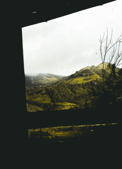 Scenic view of landscape against sky seen through glass window