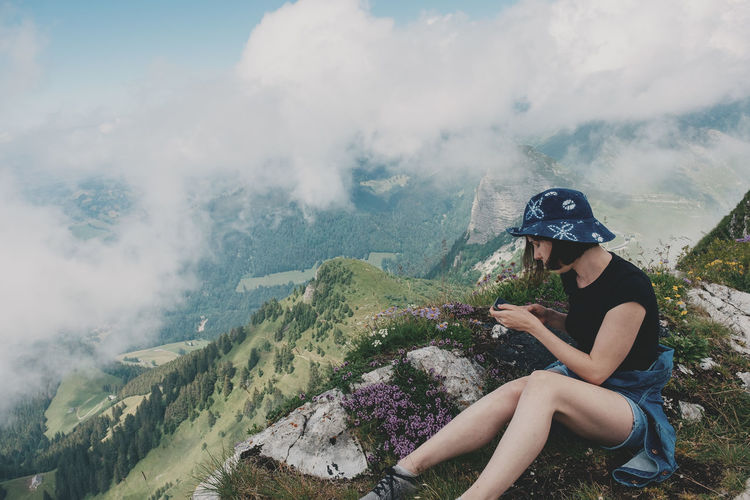 Full length of woman wearing hat sitting at cliff against cloudy sky