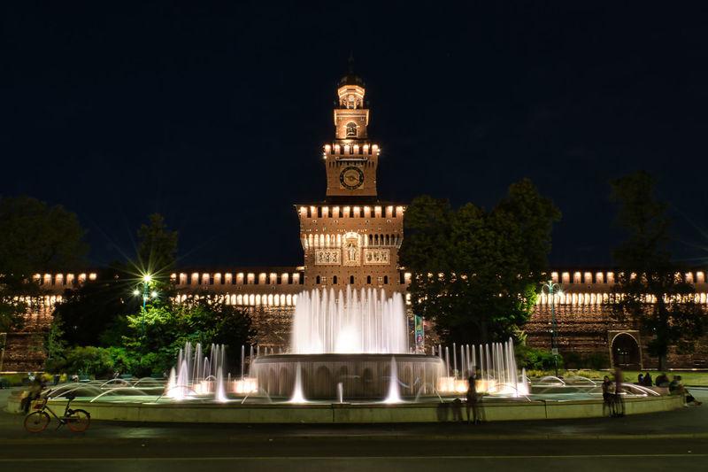 Illuminated fountain building against sky at night