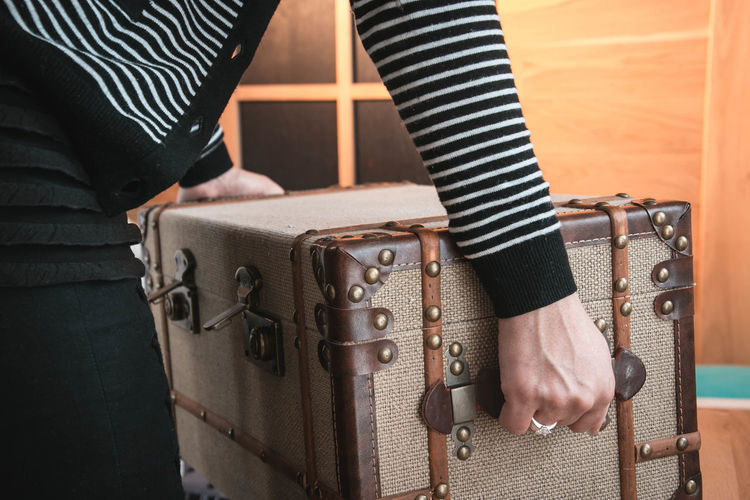 Midsection of woman holding luggage at home
