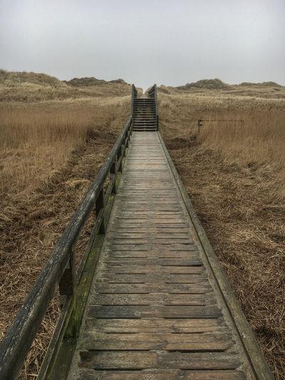 Wodden boardwalk on north sea dunes against sky in winter, st peter-ording, germany