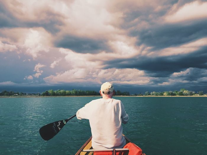 Man rowing boat in lake against cloudy sky during sunset