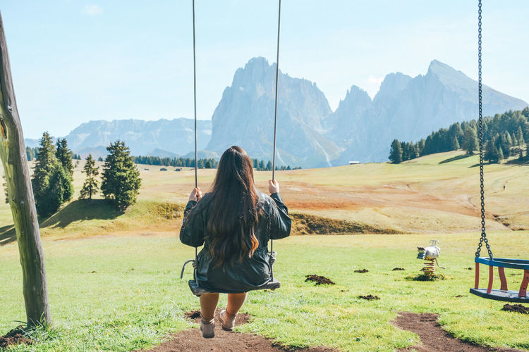Rear view of woman on swing against mountains