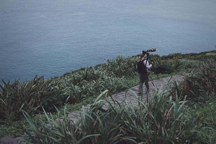Man photographing at sea shore