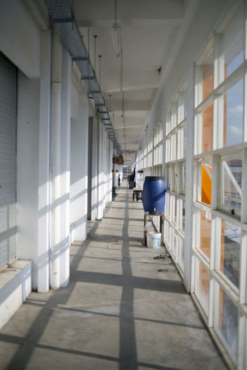 Rear view of person walking on corridor of building