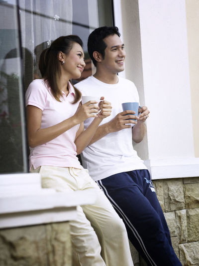 Smiling couple talking while having coffee against wall