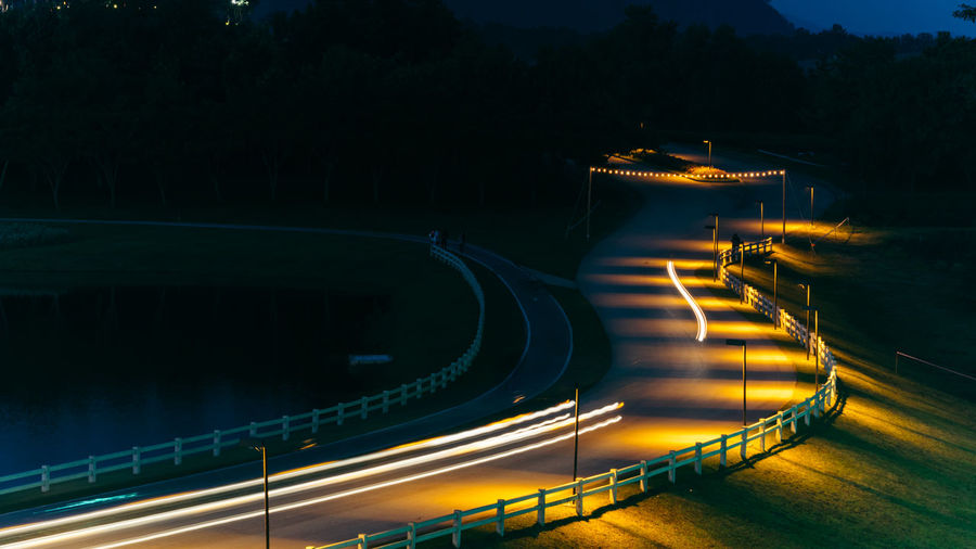 High angle view of light trails on road by lake