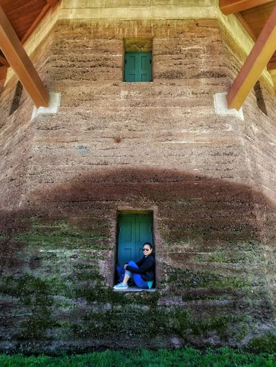 Woman sitting on window of house