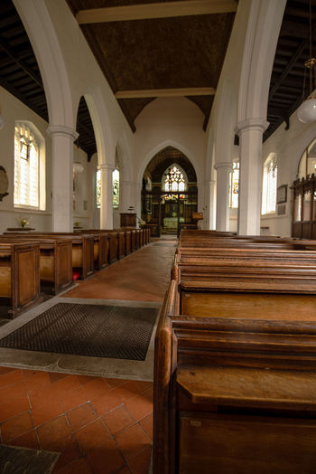 Along a church isle flanked by old wooden church pews leading to the alter and grand stained glass window. Church Stained Glass Arch Architectural Column Architecture Belief Bench Building Built Structure Ceiling Colonnade Empty Indoors  Pew Place Of Worship Religion Seat Spirituality Wood - Material
