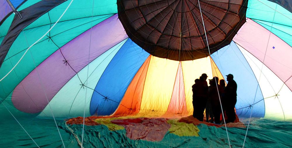 People in multi colored umbrellas against blue sky