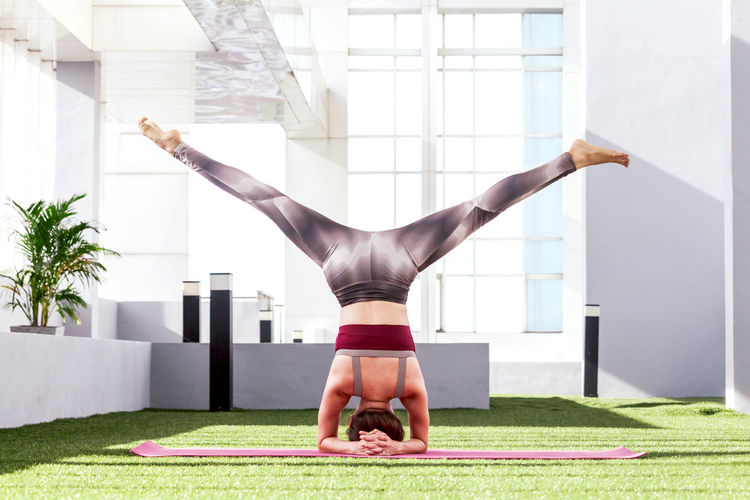 Rear View Of Young Woman Practicing Headstand On Turf